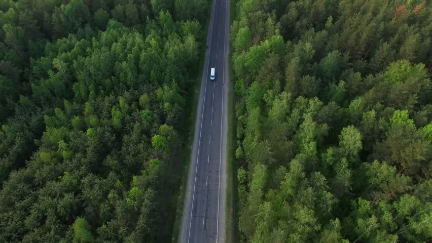 Aerial view flying over old patched two lane forest road with cars van moving green trees of dense woods growing both sides - shot with drone quad copter birds eye view perspective from above  | Shutterstock HD Video #17867818