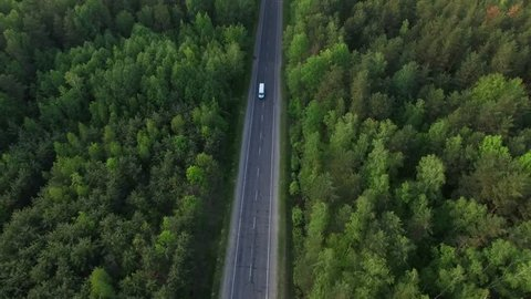Aerial view flying over old patched two lane forest road with cars van moving green trees of dense woods growing both sides - shot with drone quad copter birds eye view perspective from above