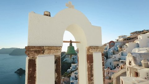 Calm sea, white church arch, cross, bells on the Santorini island, Greece.