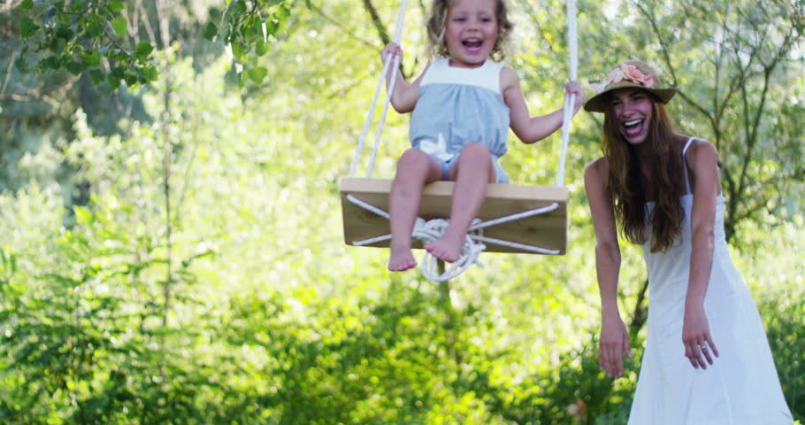 on a sunny day Mom and daughter play on the swing and both are very happy of the day spent together. Mum helps the little girl swinging on the swing.