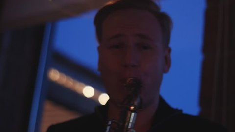Man play saxophone on party in nightclub. Performance. Look in camera. Cheering. Musician