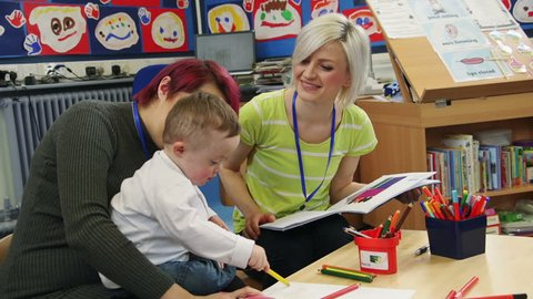 down Syndrome boy colouring at nursery while his teacher discusses his development with his mother.