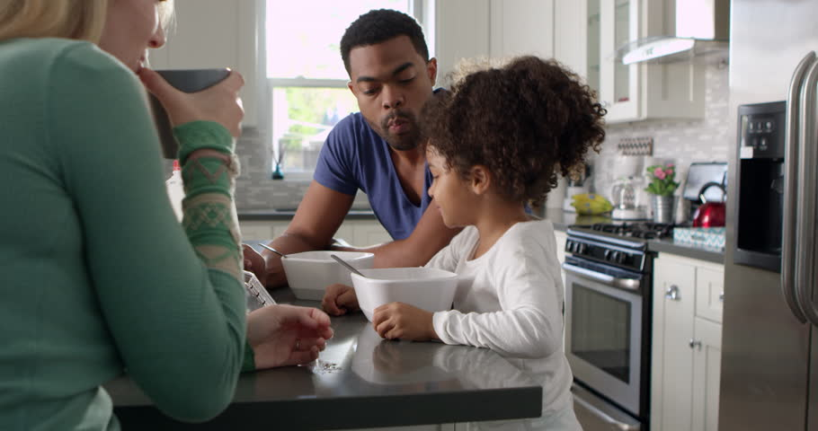 Mixed race couple and daughter eating breakfast in kitchen, shot on R3D