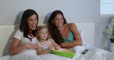 Young girl watching tv in bed with gay female parents, shot on r3d