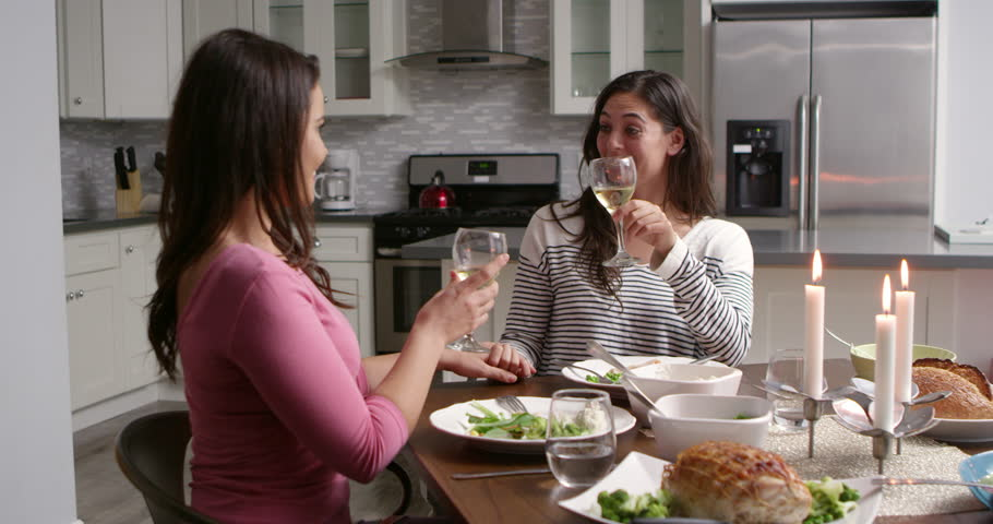 Female gay couple make a toast at dinner in their kitchen, shot on R3D