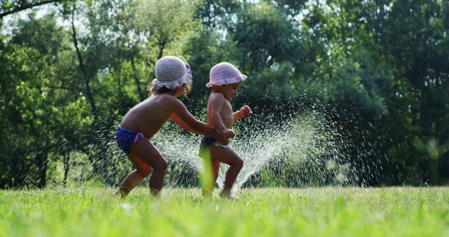 two little girls playing with a sprinkler garden , a child is small and a little girl is bigger . girls are friends and play with the cool water in the hot sunny day. they're happy sisters. nature