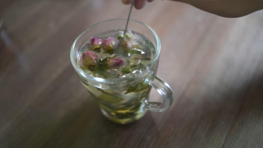 Green flower tea in the glass - mixing spoon | Shutterstock HD Video #17926858