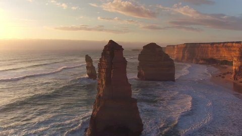 AERIAL: Magnificent Twelve Apostles standing in shallow ocean water along the majestic rocky shore. Famous Australian coast with high rocky cliffs and limestone Apostles pillars at golden sunset