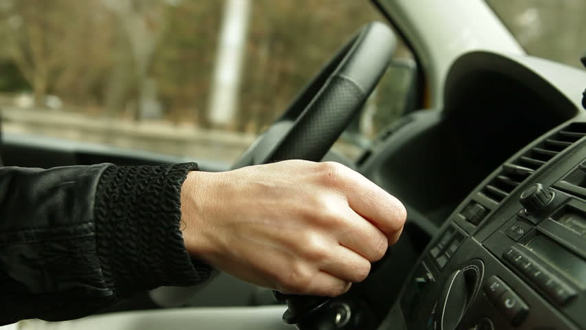 woman driving car on city street, focus on hand on the gearshift