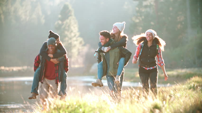Five friends have fun piggybacking by a rural lake