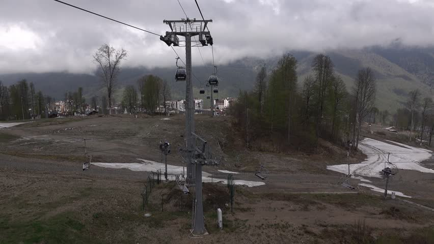 Panoramic view of alpine ski resort in low season. Empty ski lift cabins ride over dark dirty mountain slopes, bare trees, pine trees and melting snow banks. POV view from ropeway carriage