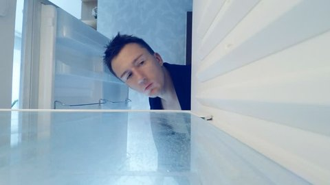 Young man sleepily opens an empty fridge and looking sad