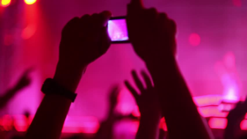 Hands hold camera with digital display among people at rave party with pink red light, view from behind