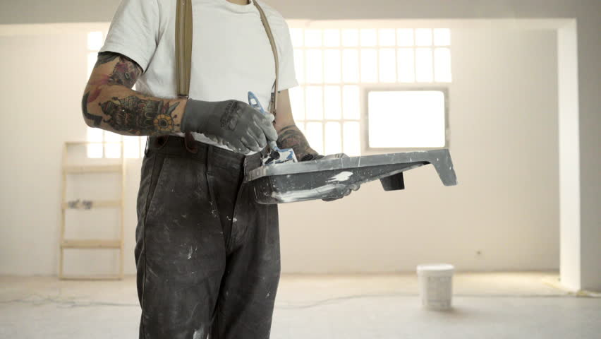 Closeup, unrecognizable tattooed man wered pants with suspenders is preparing to paint wall with brush and white paint Home diy renovation