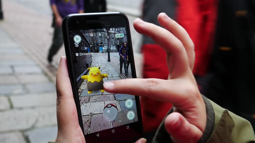 "ABERDEEN, UNITED KINGDOM - JULY 15, 2016: People playing ""Pokemon GO"" the hit augmented reality smart phone app while trying to find Pokemon on July 15, 2016 in Aberdeen, United Kingdom."