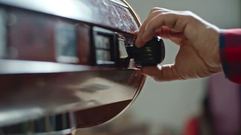 Closeup tilt down of coffee shop barista activating espresso machine steam wand to by turning steam valve knob, slow motion shot on Sony NEX 700