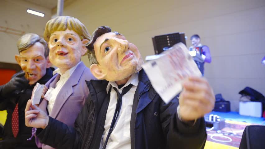 Person with Borut Pahor mask showing 500 Euro banknote 4K. Slovenian carnival with political satire mocking president Borut Pahor, Angela Markel and prime minister Miro Cerar.