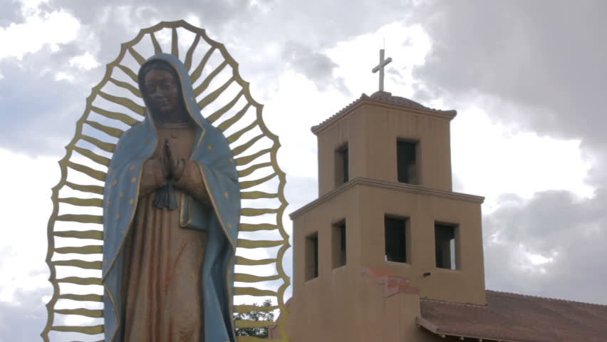 Wide shot of a statue of the virgin of Guadalupe standing serenely in front of an adobe church. Ominous storm clouds gather behind the religious icon and the Mexican Catholic church.