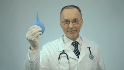 Happy smiled proctology doctor showing rubber syringe and looking at camera