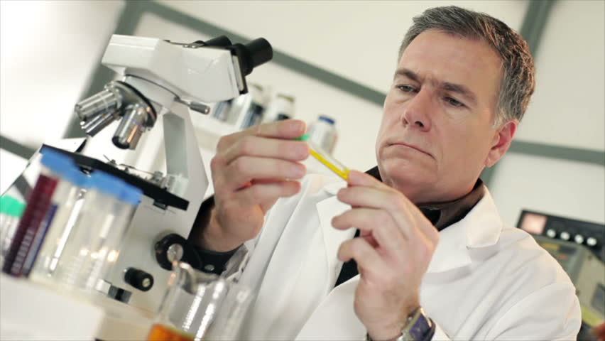 A handsome mature scientist or chemist sitting in a laboratory visually examining a liquid he has in a test tube.