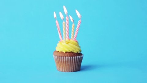 holiday, celebration, greeting and party concept - birthday cupcake with five burning candles over blue background