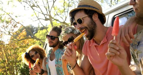 Group of hipster friends enjoying and eating ice cream at a music festival