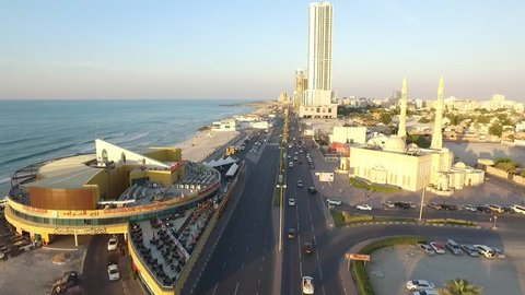 AJMAN, UAE - CIRCA NOVEMBER 2015: Cityscape of Ajman with modern buildings aerial top view and traffic on road. Coastline with beach and gulf. Sunset time. Ajman is the capital of the emirate of Ajman