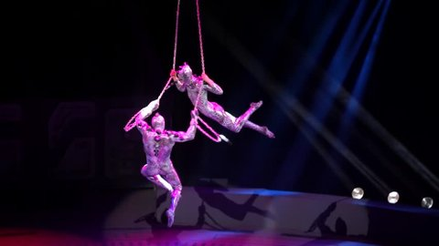 """ST. PETERSBURG, RUSSIA - JANUARY 2, 2016: Brothers Zapashny circus, """"UFO. Alien Planet Circus"""" show in Saint Petersburg. Two aerial gymnasts perform in the air and descend on the stage."""