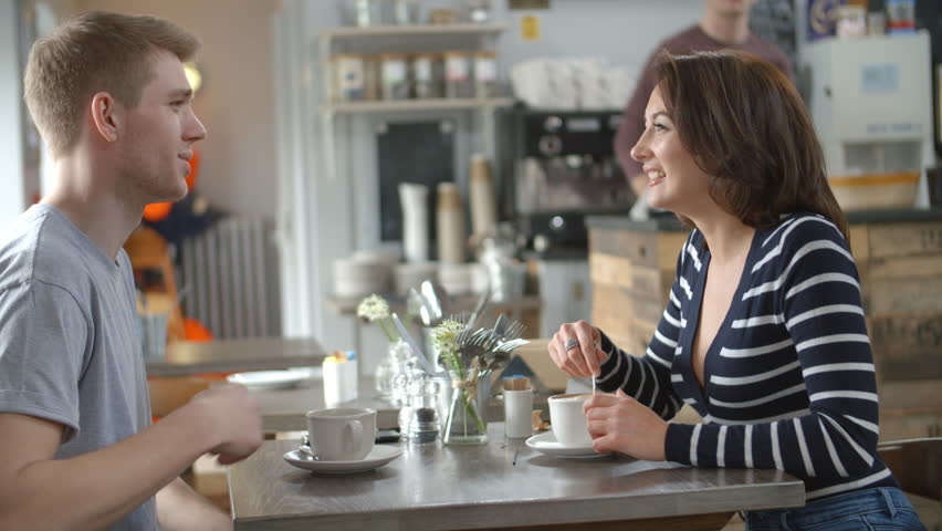 Adult couple talking at a table in a coffee shop, side view | Shutterstock HD Video #18149239