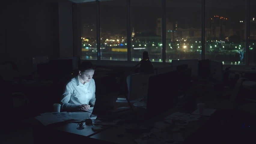 Exhausted sleepy woman sitting at desk in dark office at night and working on laptop, drinking coffee and rubbing neck to concentrate, wide shot on Sony NEX700 + Odyssey 7Q