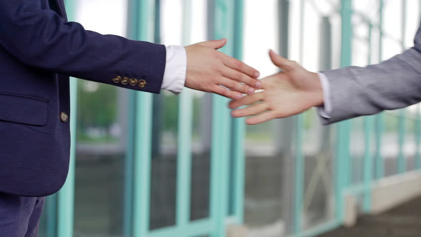 Close up of handshake greeting of two business partners, business centre background. Slow motion.