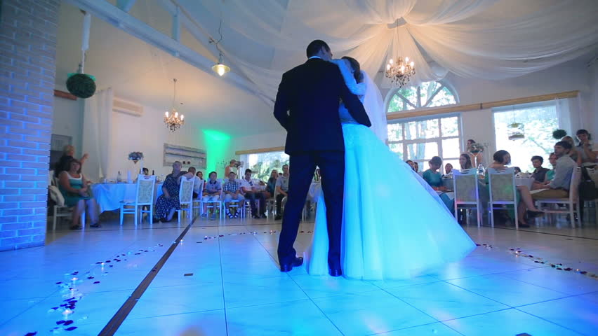 Beautiful delicate bride and handsome groom dancing first dance at the wedding party in hall with colored lights. 31.08. 2015, Lviv, Ukraine