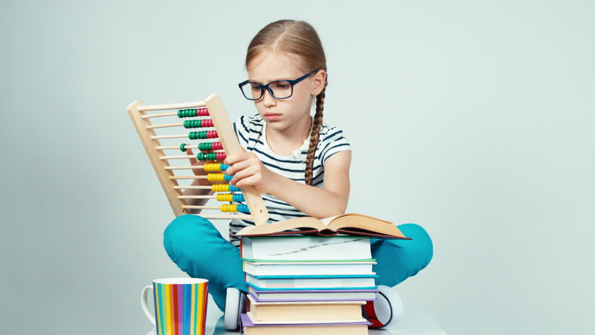 Portrait girl 7-8 years old using abacus and sitting near stack of books and smiling