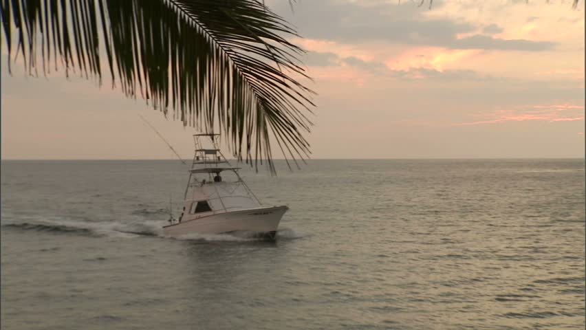 Sport fishing boat entering harbor at sunset