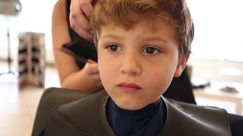 Young boy having a haircut at the barbershop. Kid getting a haircut | Shutterstock HD Video #18279478