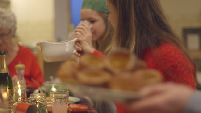 A family enjoy their Christmas dinner at the table together. One of the family members is passing around a plate of Yorkshire puddings for everyone to share. | Shutterstock HD Video #18293647