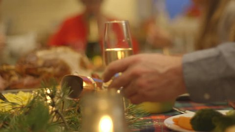 A family raise their glasses at the dinner table to celebrate Christmas day. The adults have glasses of prosecco and the children have juice.