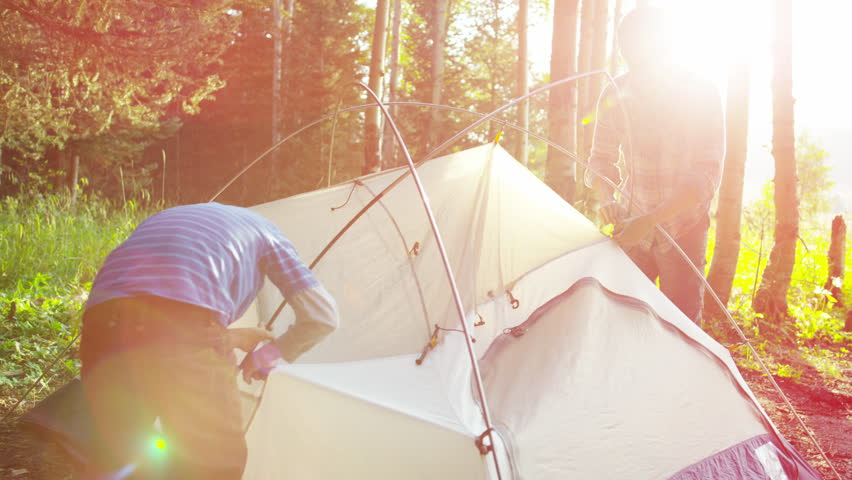 Happy Caucasian father teaching son assemble tent on Summer holiday outdoors