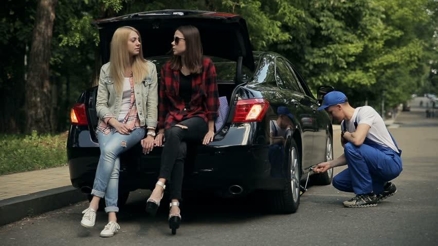 Girls sitting on trunk while mechanic fixes car | Shutterstock HD Video #18323347