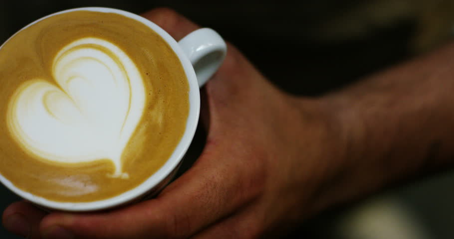 a bartender makes an artistic composition with fresh milk to make a cappuccino Italian quality, using Italian espresso. Italian concept, passion for work, breakfast and love for coffee and art.