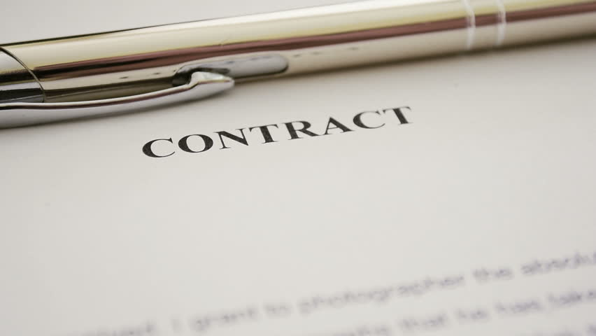 """Contract abstract. Signing contract. """"Contract"""" header on the sheet of paper, the person signs a document. Title """"Contract"""" is printed in bold text. Texture of paper, closeup view."""
