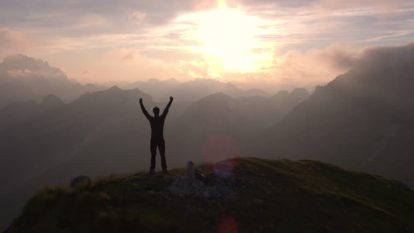 Aerial - Flyover silhouette of a man standing on top of the mountain. Man raising arms victoriously after climbing the mountain | Shutterstock HD Video #18379711