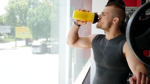 Young guy bodybuilder drink protein cocktail during hard training muscles in gym