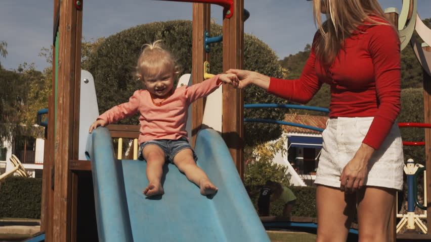 Mother and little girl on slide in playground | Shutterstock HD Video #18403978
