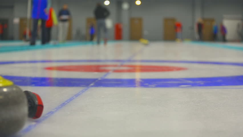 Curling player delivering a stone on a curling rink, sliding over the ice, shallow DOF