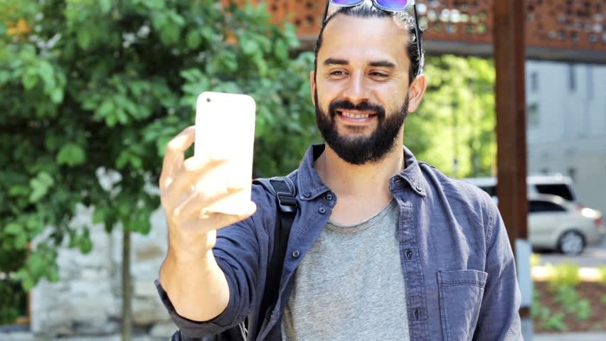 travel, tourism, communication, technology and people concept - smiling man with backpack taking video or selfie by smartphone on city street #18418018