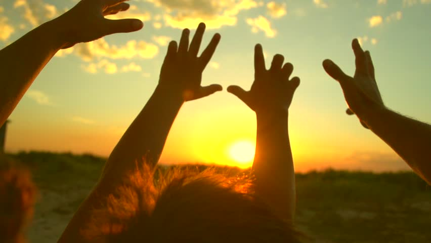 Happy family raising hands up, Father, mother and little son together enjoying nature outdoors. Hands silhouette over sunset sky. Vacation concept. Slow motion 240 fps. Full HD 1080p