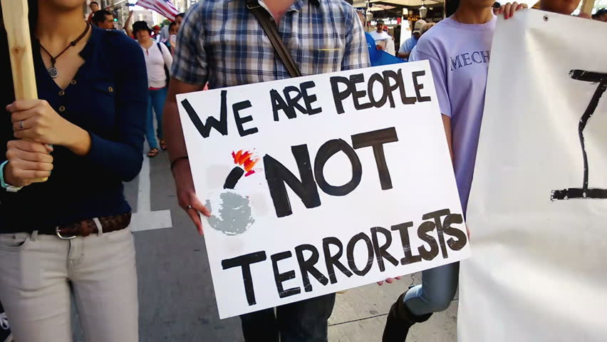 """We Are People Not Terrorists"" Rally Sign. A white picket sign that reads, ""We Are People, Not Terrorists"" is held up during an immigration rally in downtown Los Angeles on September 22, 2013."