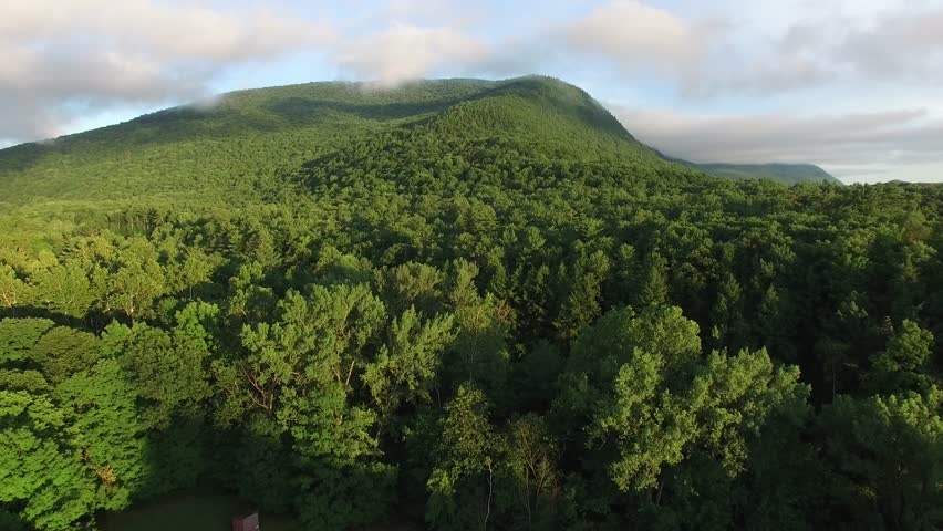 4K aerial shot climbing slowly up the side of a mountain surrounded by clouds | Shutterstock HD Video #18444853