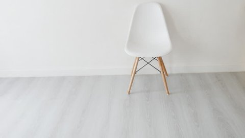 Conceptual Empty White Wooden Leg Chairs with white wall and gray wooden floor and copyspace, panning